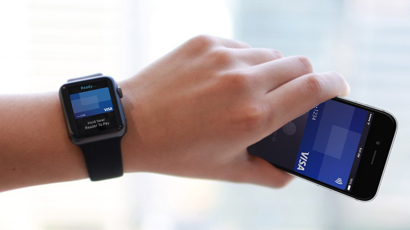 A left hand holding a mobile phone with a Visa card visible on its screen and an Apple watch on the wrist.