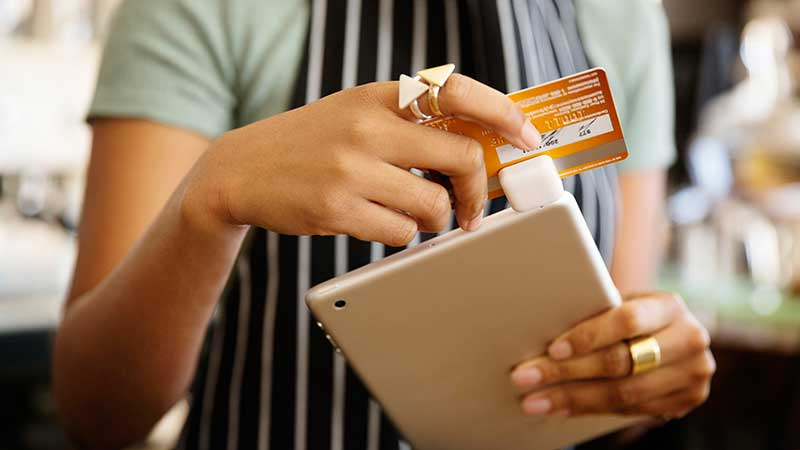 A waitress swipes a Visa card through a Square reader attached to a tablet.